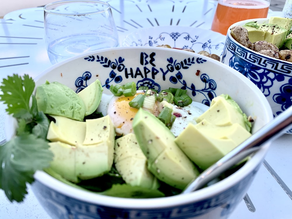 sliced green fruit on white and blue ceramic bowl
