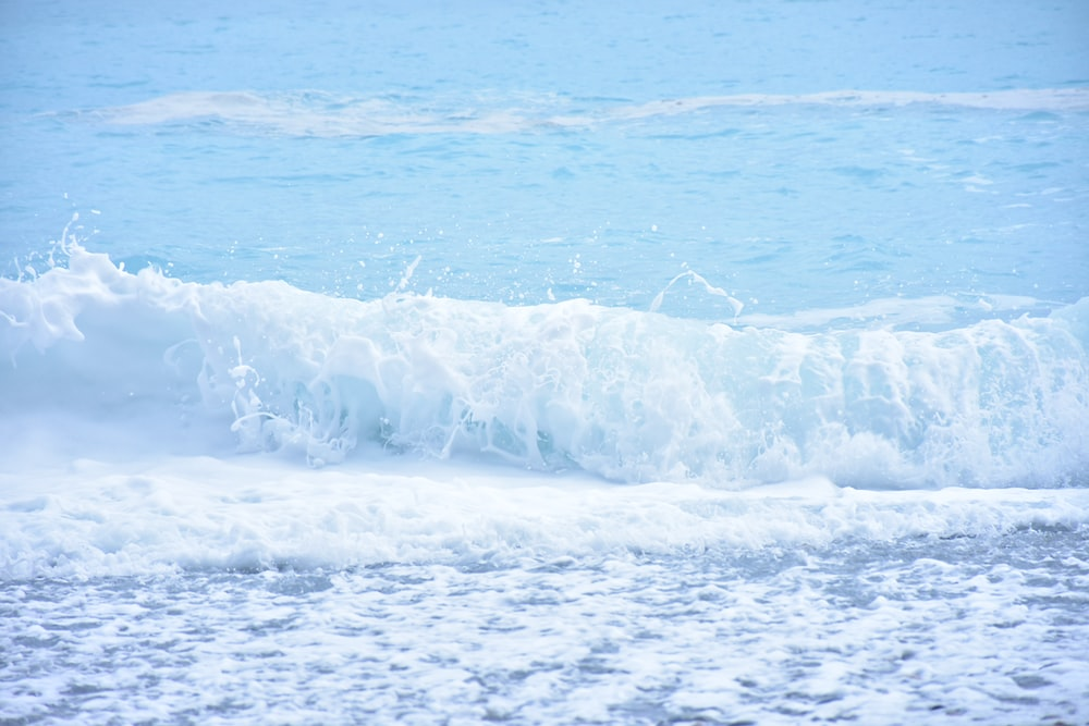 white waves on blue sea during daytime