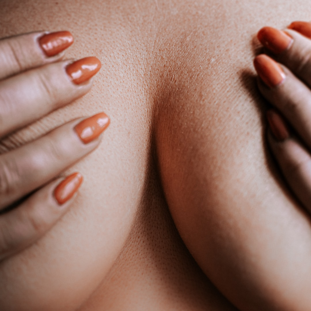 Womans breast and hands detail - stop the cancer