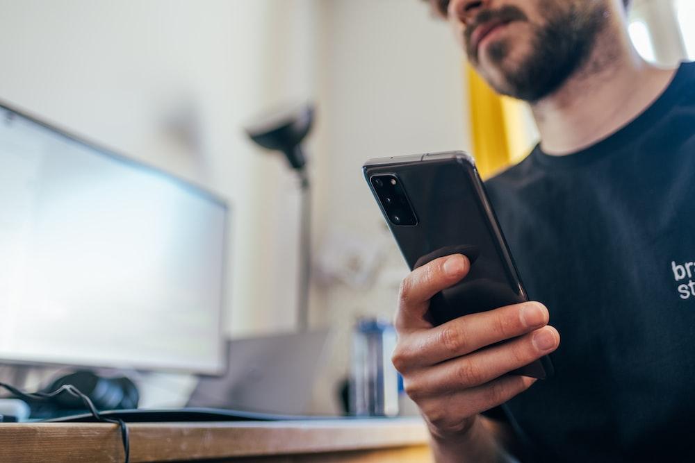 man in black crew neck shirt holding black iphone 5