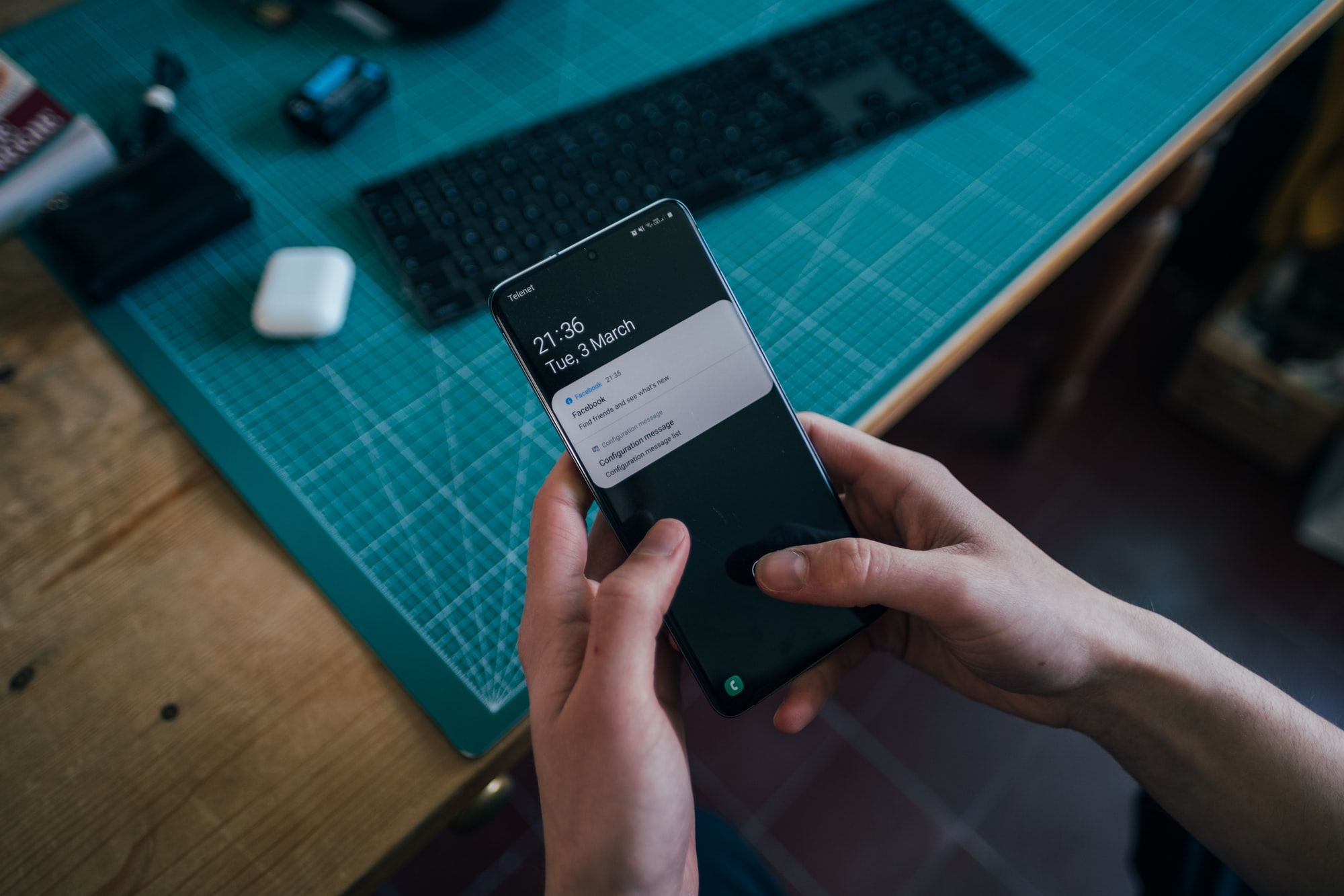 Young man holding phone in his hands at a desk. There are notifications on screen.  Picture taken by Jonas Leupe (www.brandstof.studio) for Tandem Tech (www.tandemtech.be)