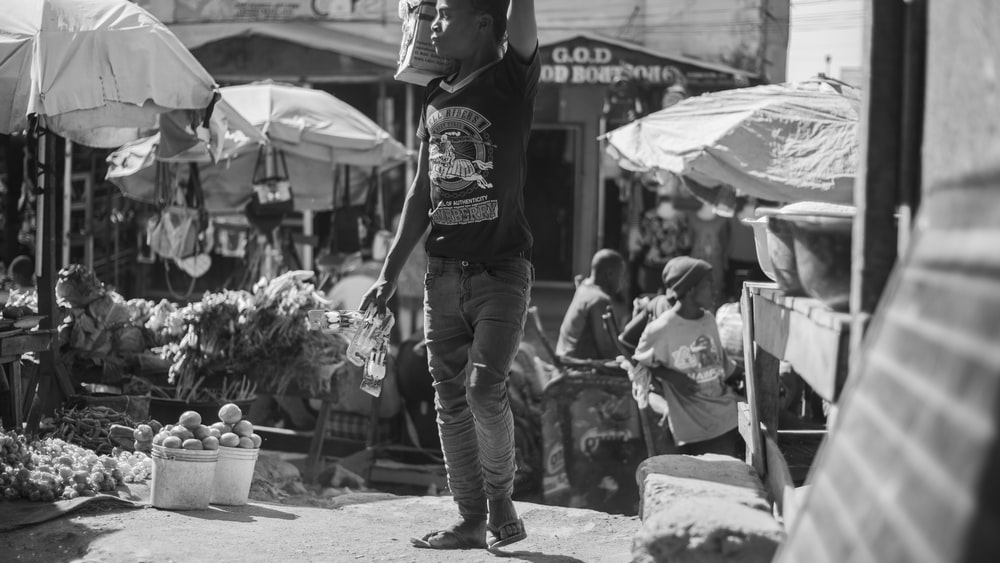man in black t-shirt and blue denim jeans standing on street