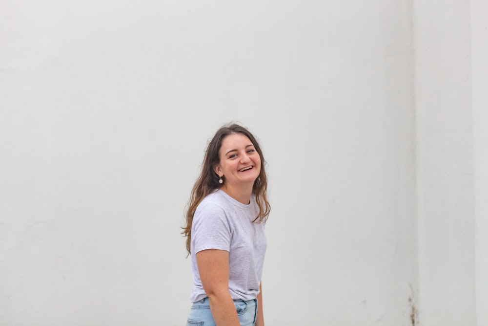 woman in white crew neck t-shirt and blue denim shorts smiling