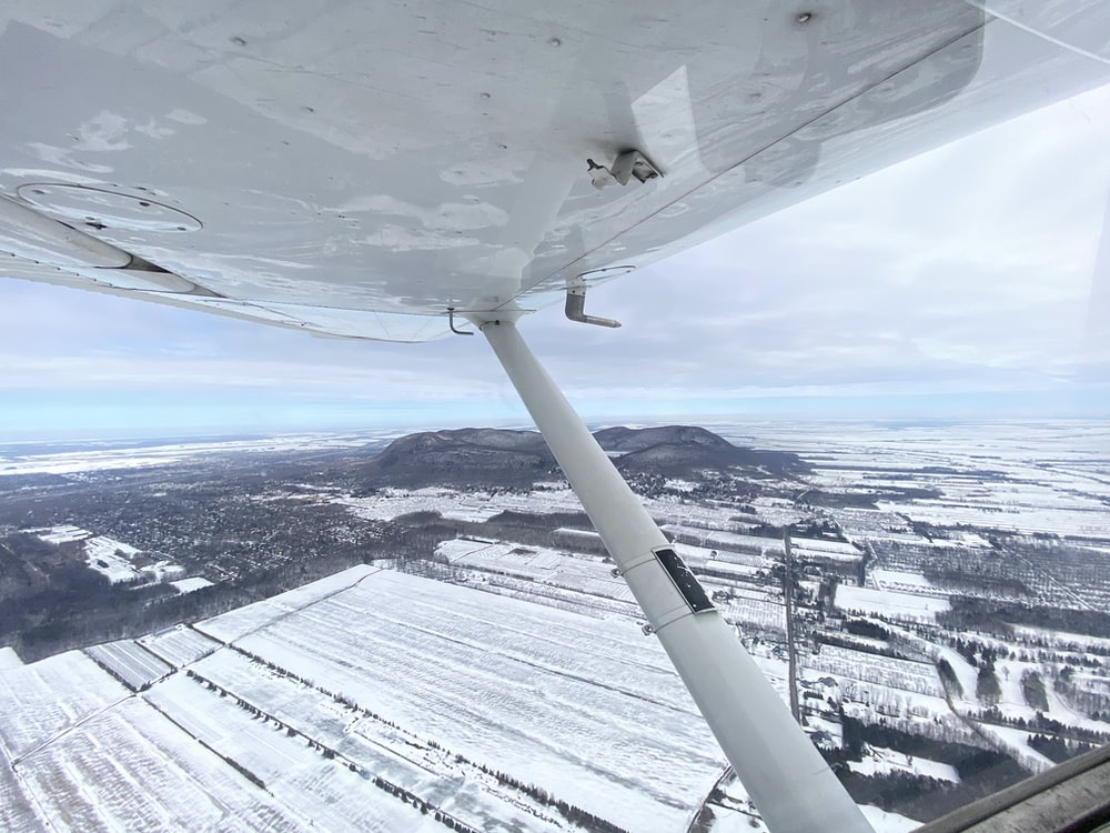 white airplane flying over snow covered mountains during daytime