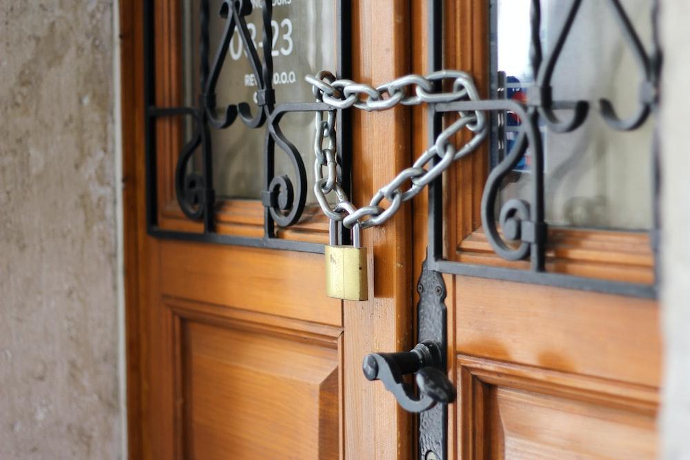 grey metal chain on brown wooden door