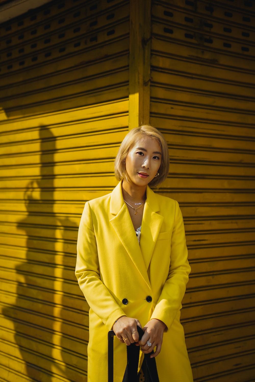 woman in yellow blazer standing beside yellow wooden wall