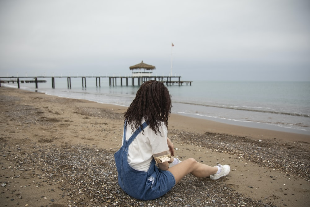woman in white shirt and blue denim shorts sitting on beach shore during daytime