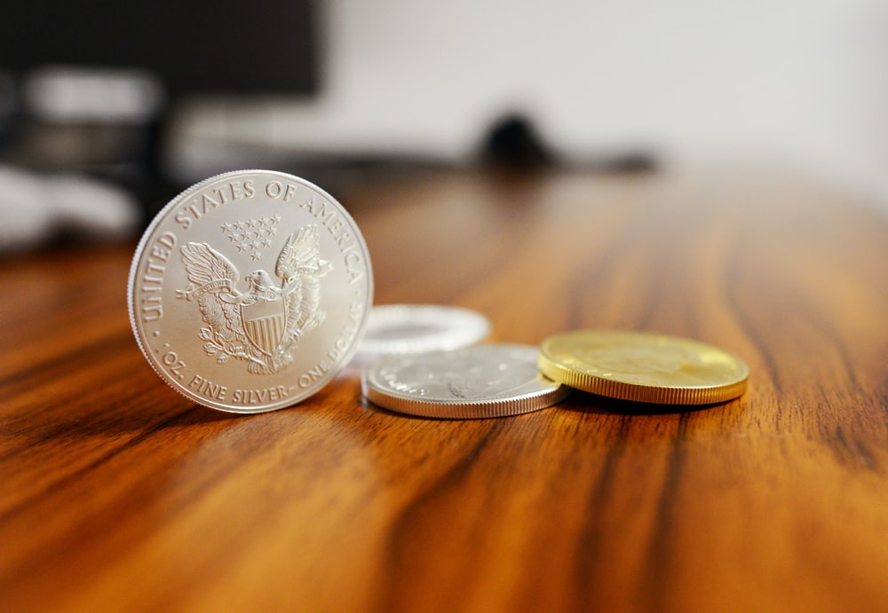 silver round coins on brown wooden table