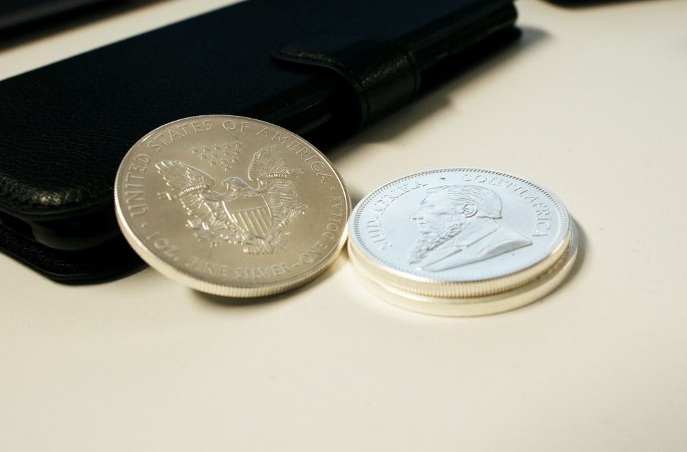 silver round coins on white table