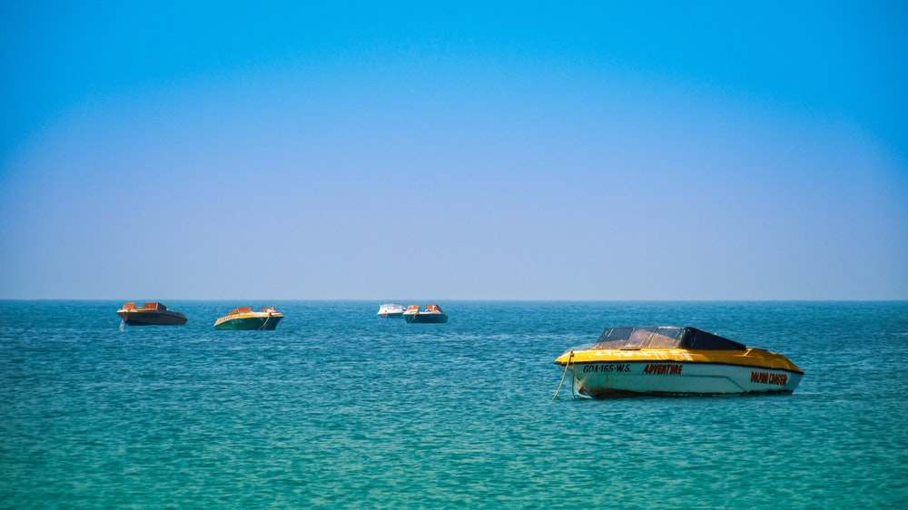 brown and white boat on sea under blue sky during daytime