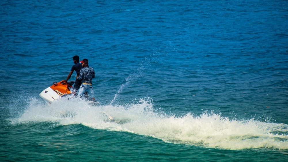 2 men surfing on sea during daytime