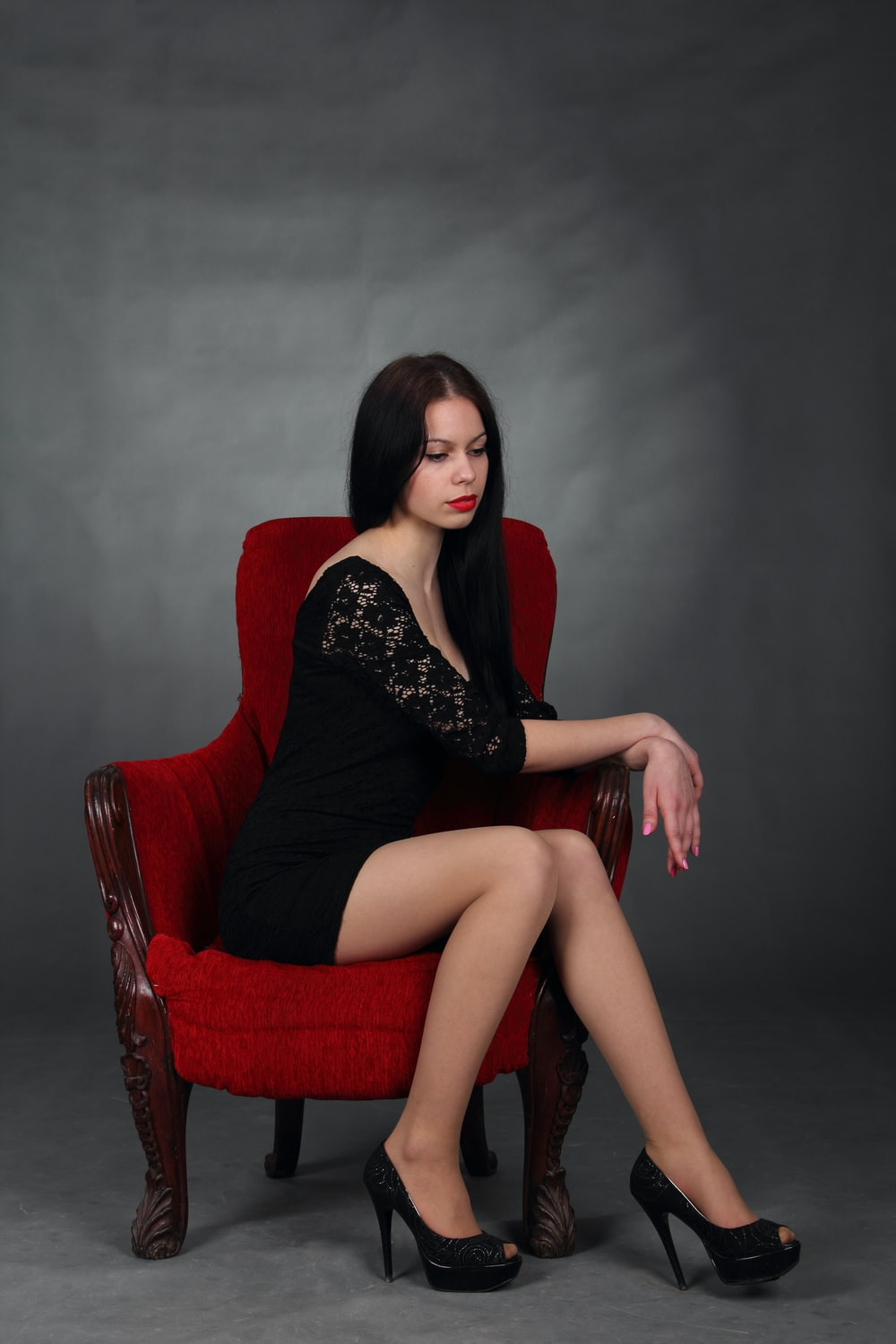woman in black dress sitting on red armchair