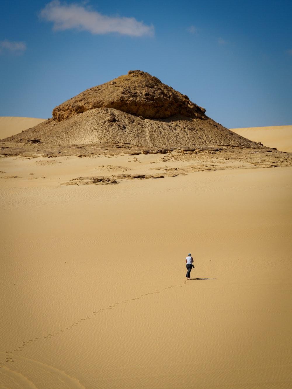man in white shirt walking on brown sand during daytime