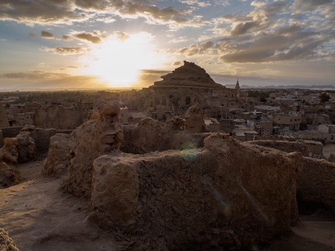 the sun is setting over the town of Siwa, the most remote city of all Egypt, in the middle of the desert
