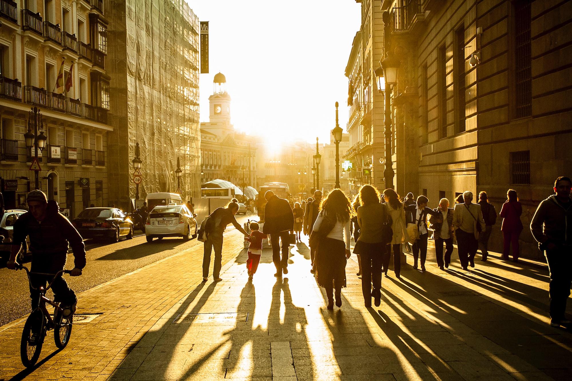 Street in Madrid, golden hour. people walking, bike