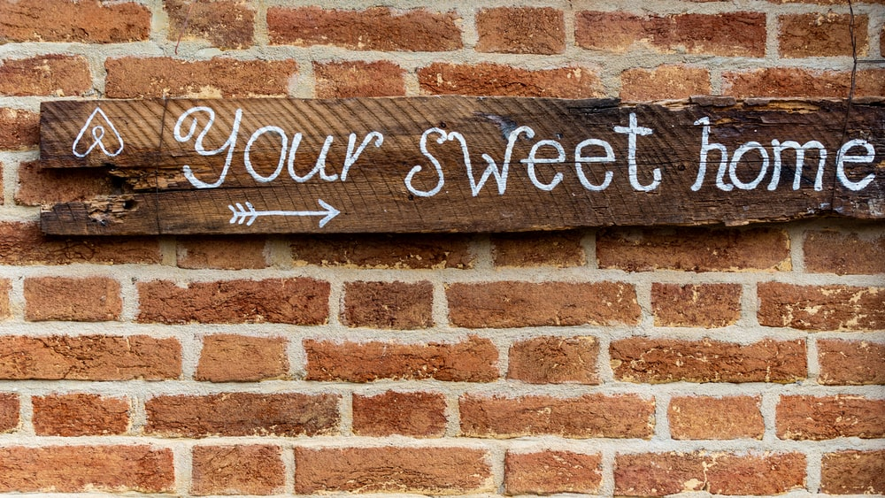 brown brick wall with welcome to the beach signage