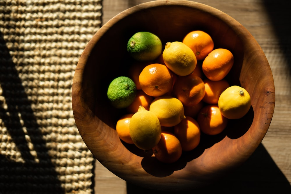yellow citrus fruit on brown wooden bowl