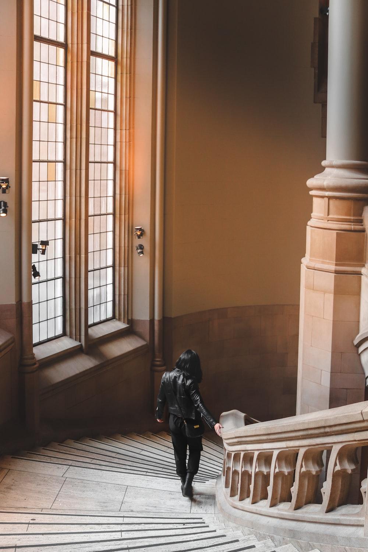 person in black jacket standing near brown wooden door