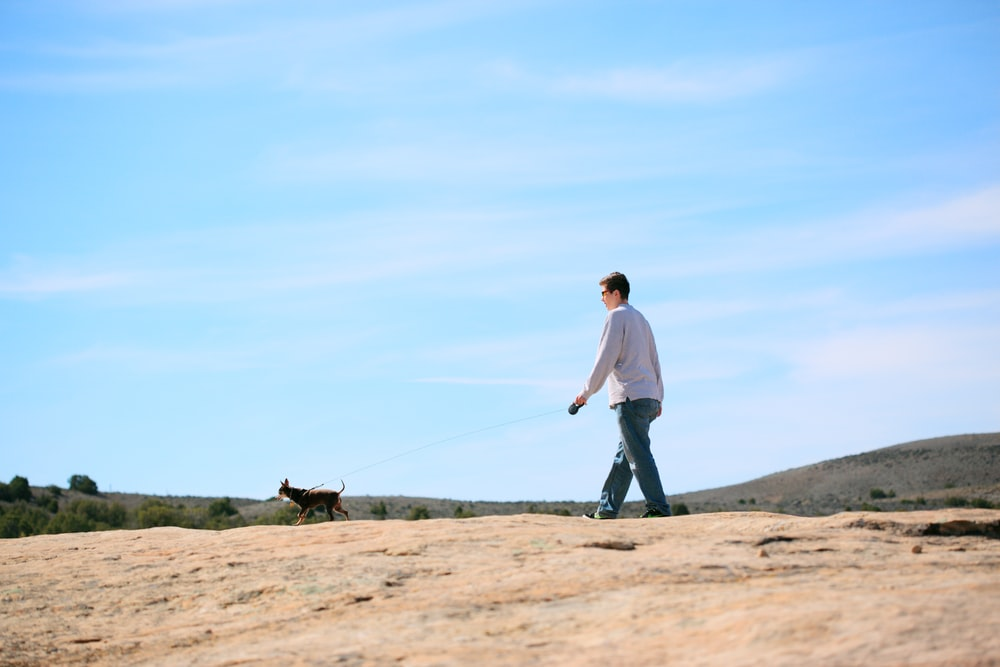 man in white long sleeve shirt and black pants walking with black dog on brown field