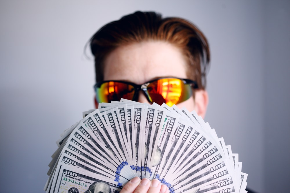 man in black framed sunglasses holding fan of white and gray striped cards