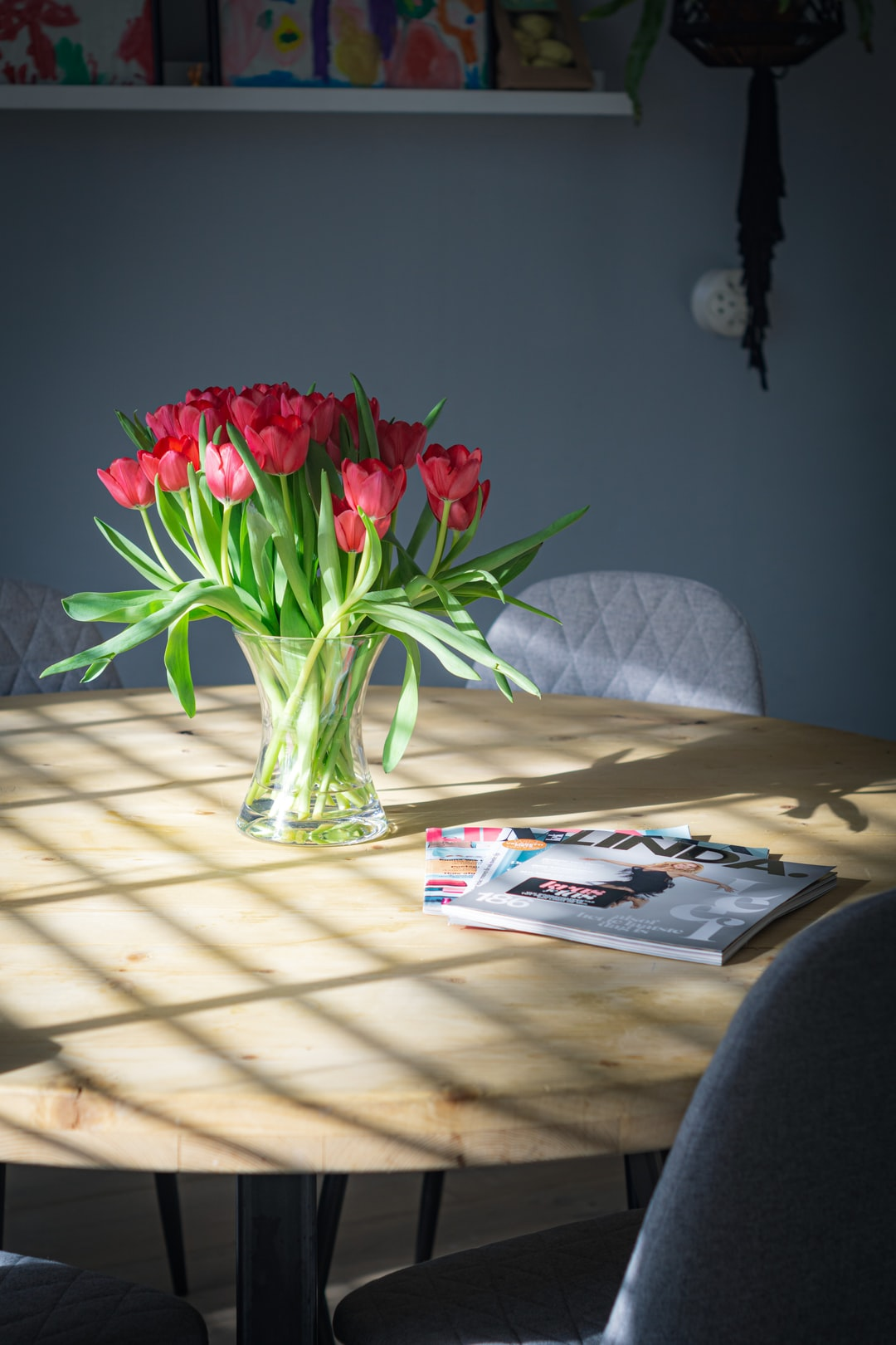 Tulps and some magazines on the dining table.