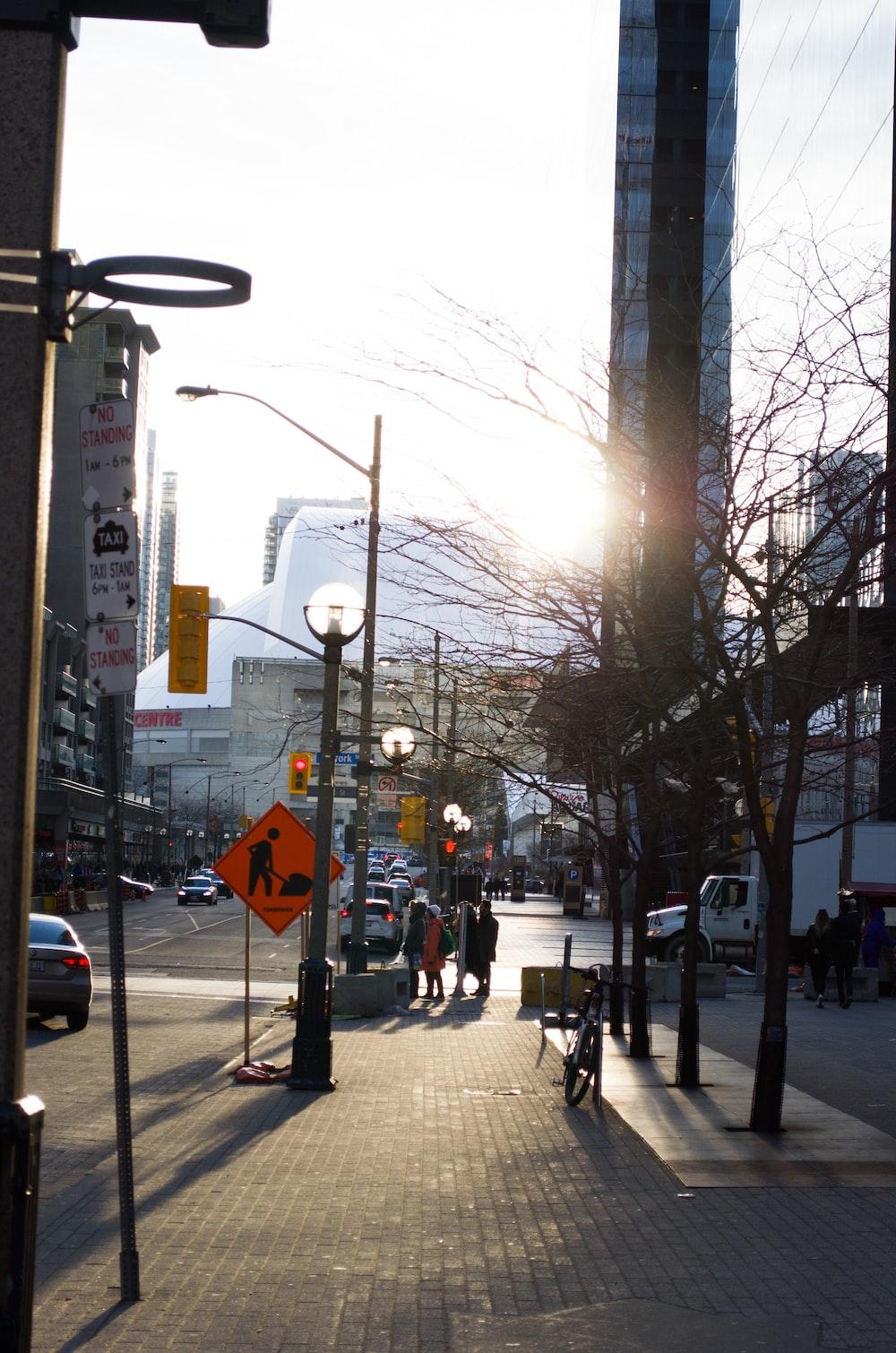 people walking on sidewalk near street light during daytime