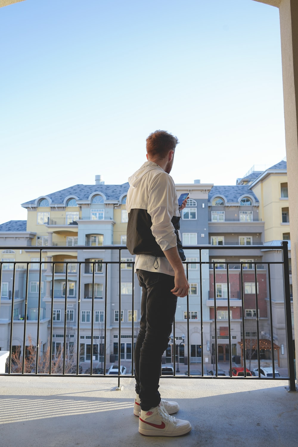 man in white dress shirt and black pants standing on top of building during daytime