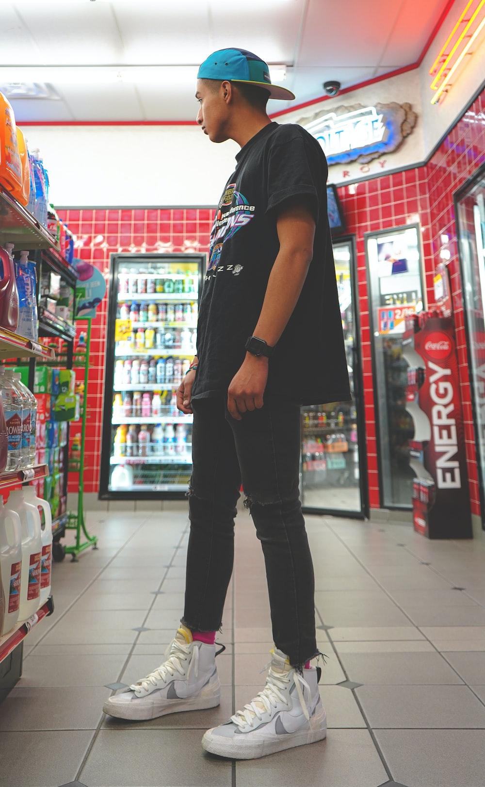 man in black t-shirt and blue denim jeans standing on white tiled floor
