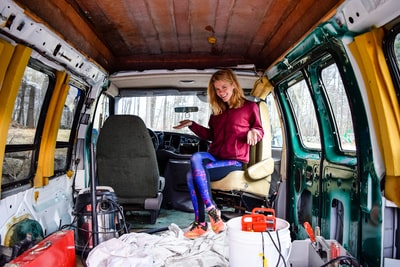 woman in red long sleeve shirt and blue denim jeans sitting on green van new hampshire teams background