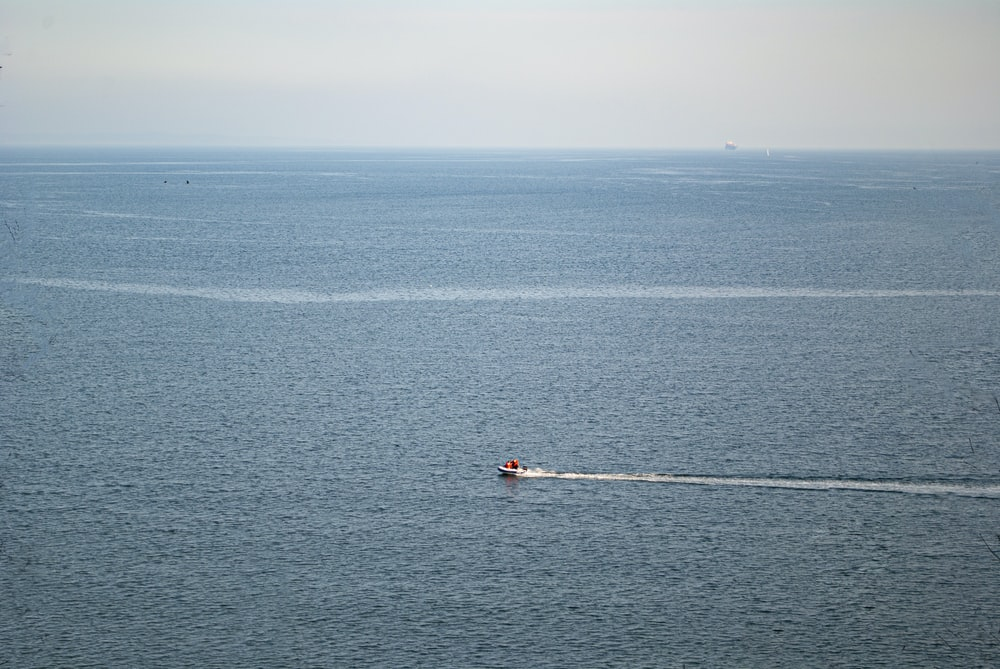 person in red shirt riding on white boat on blue sea during daytime