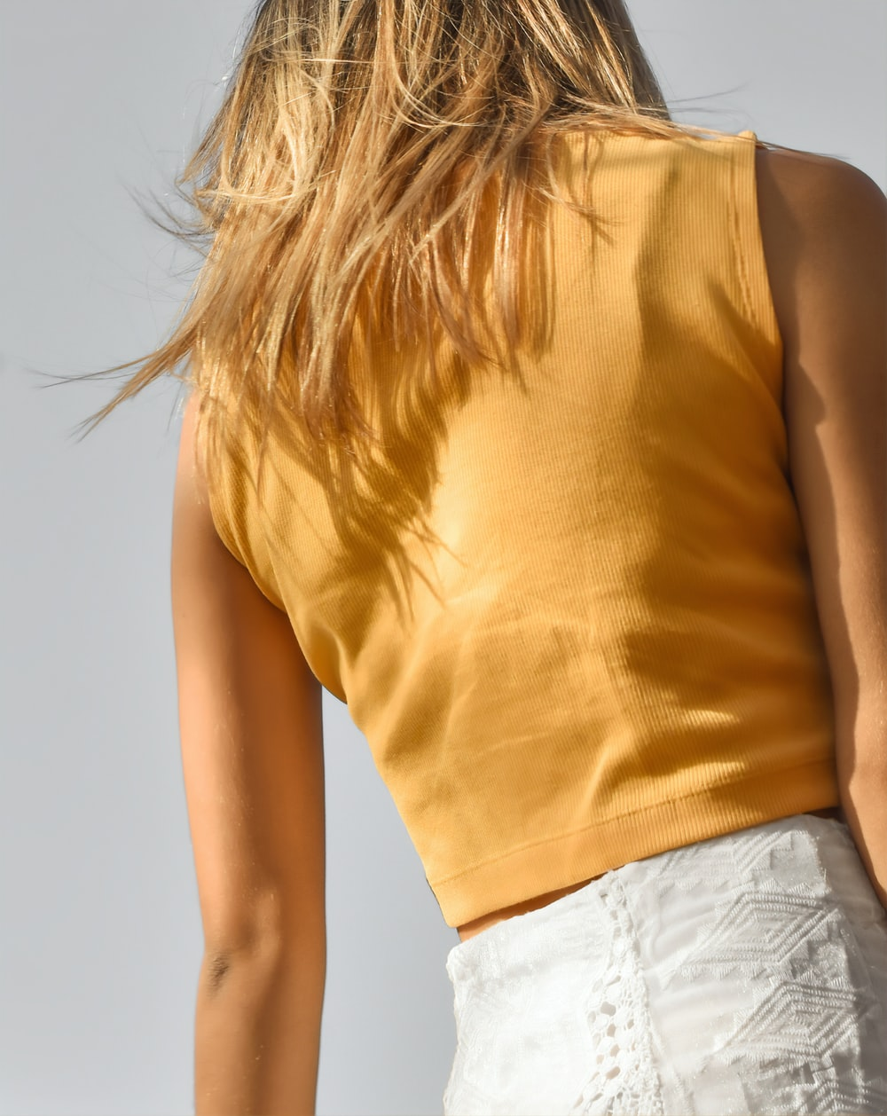 woman in yellow tank top and white denim shorts
