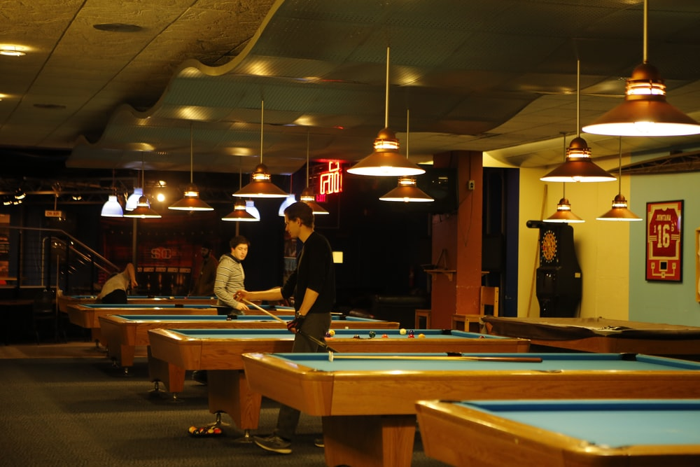 man in black shirt and brown hat standing near pool table