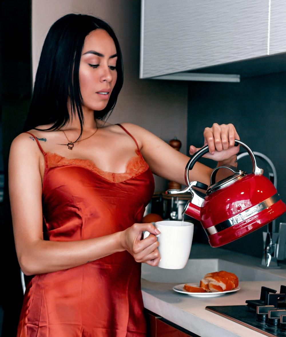 woman in red spaghetti strap dress holding white ceramic mug