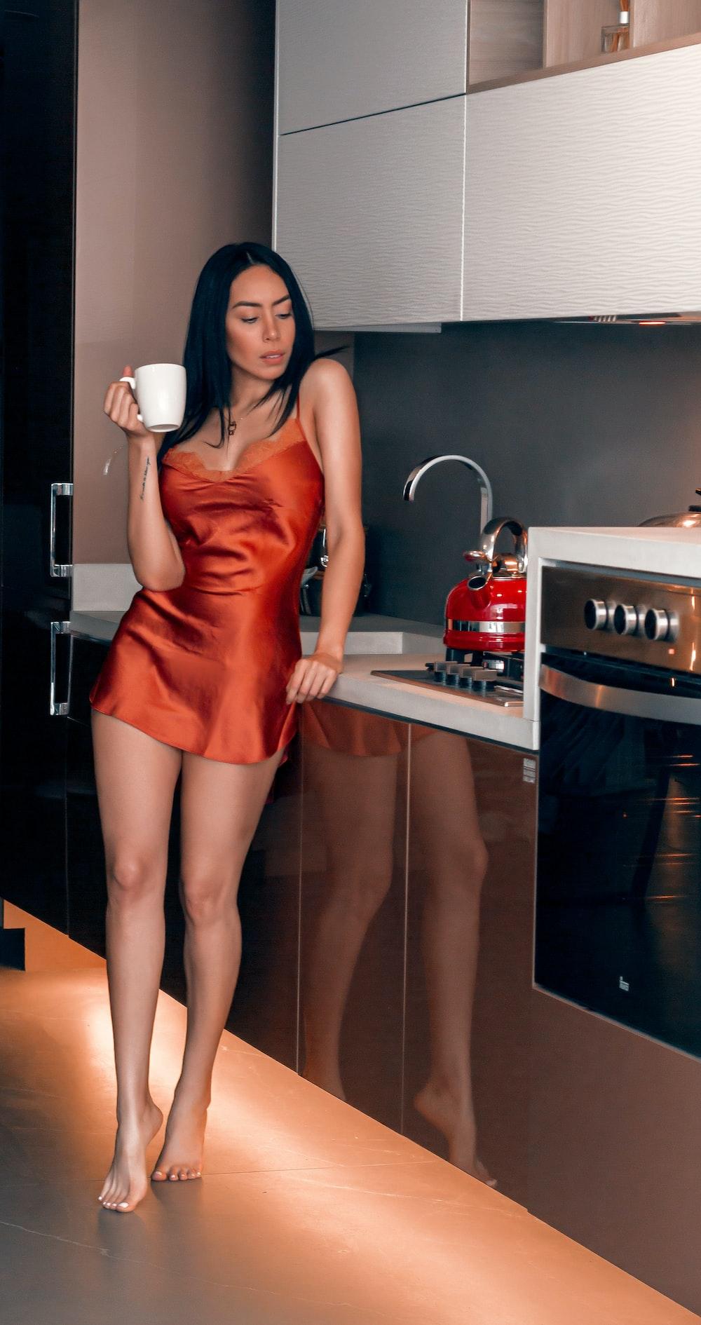 woman in red mini dress holding white ceramic mug