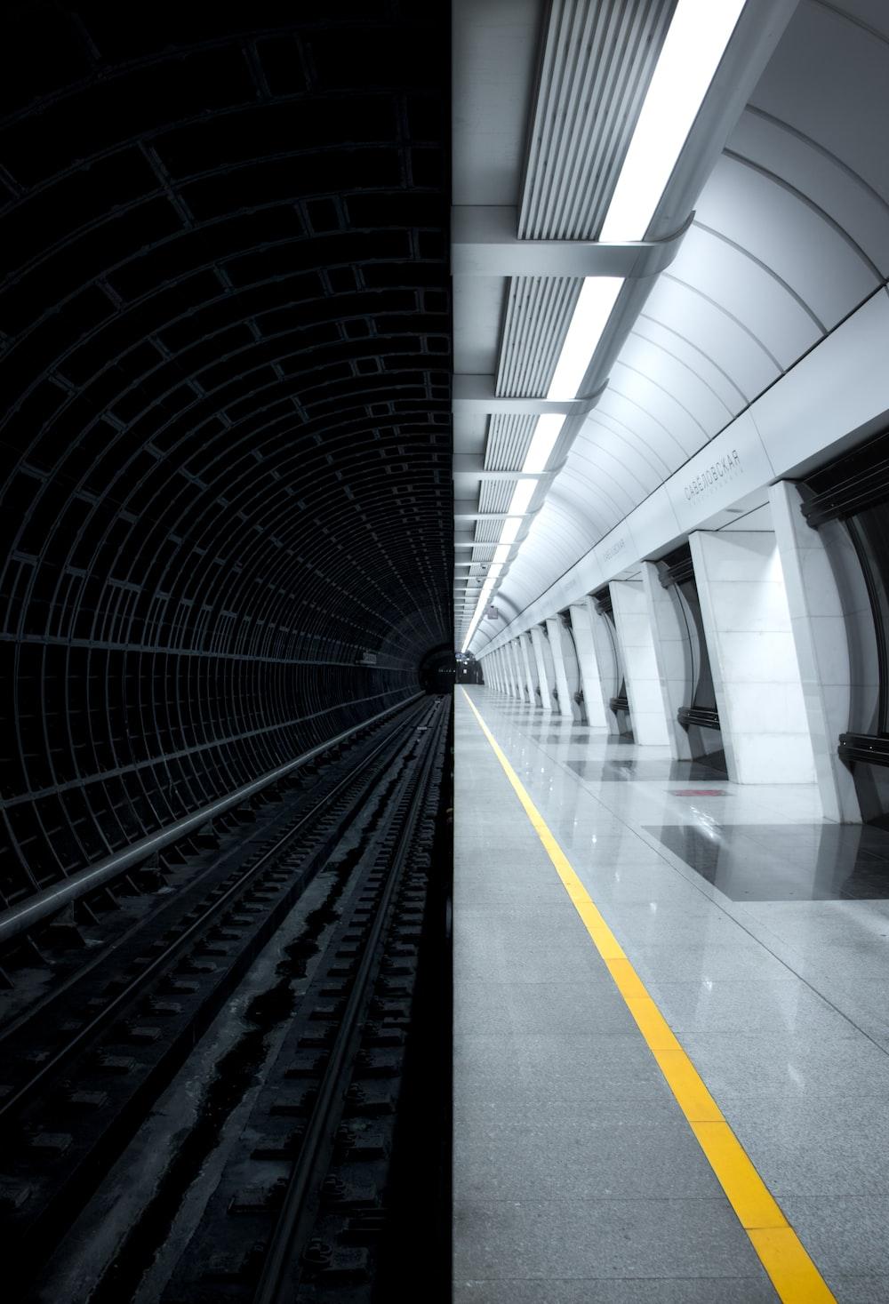 black train rail in tunnel