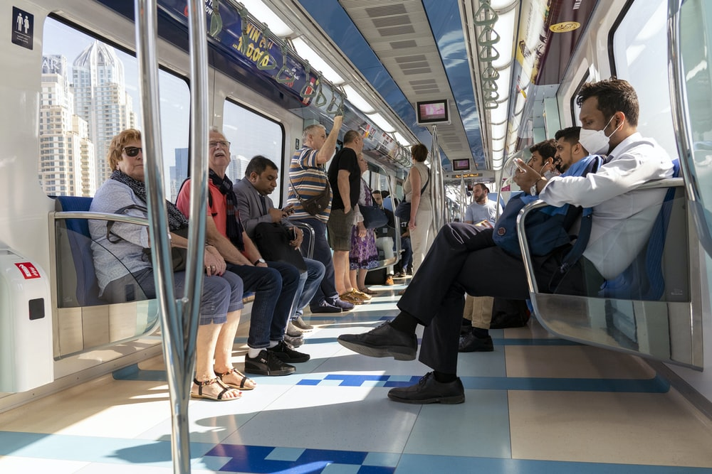 people sitting on blue and white train seat