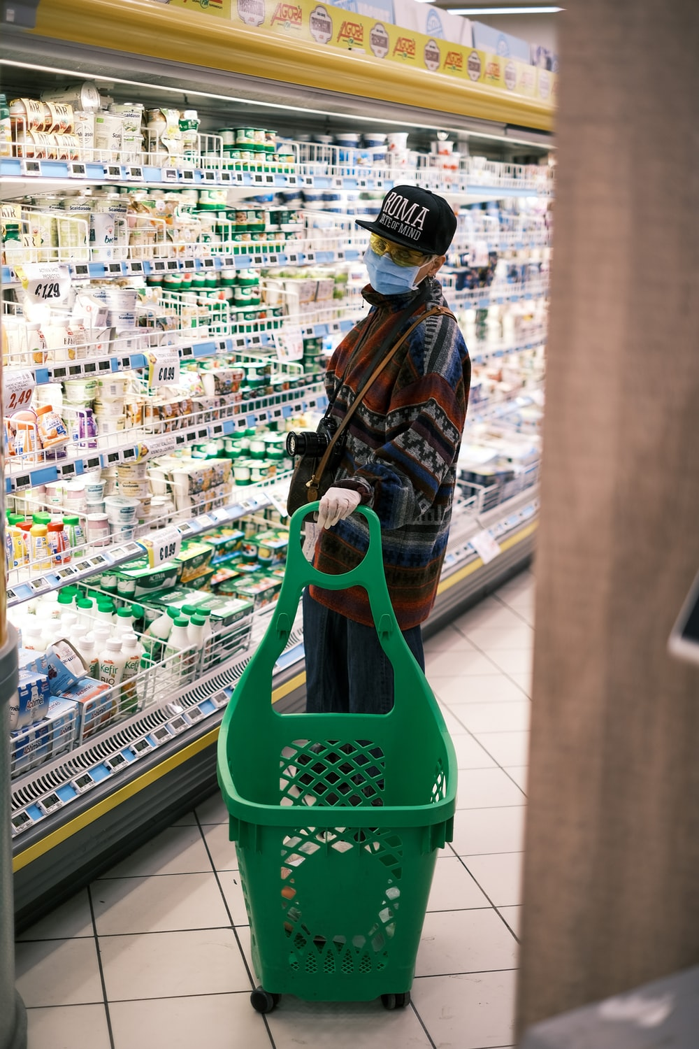 woman in brown and black jacket holding green plastic shopping basket