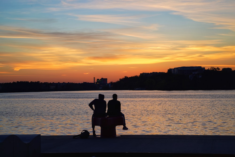 silhouette of man and woman sitting on dock during sunset