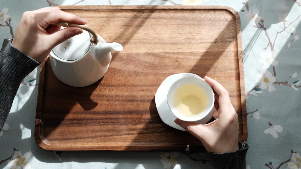 white ceramic teapot on brown wooden table