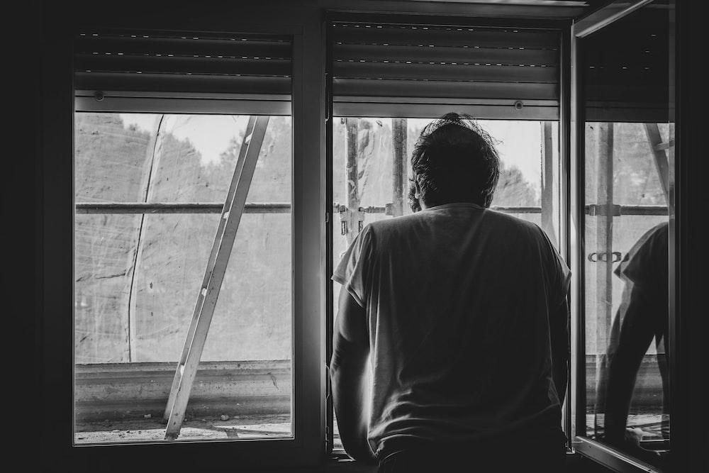 grayscale photo of man in white shirt standing near window