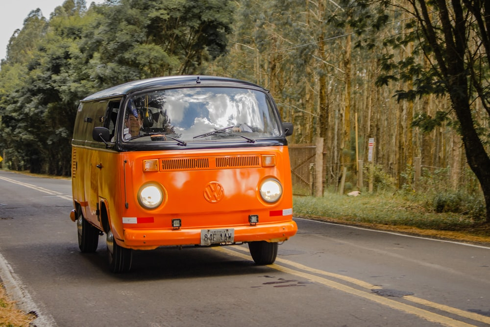 orange and white volkswagen t-2 van on road during daytime