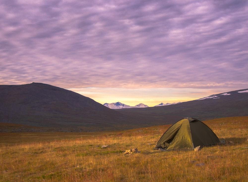 gray tent on green grass field under gray cloudy sky