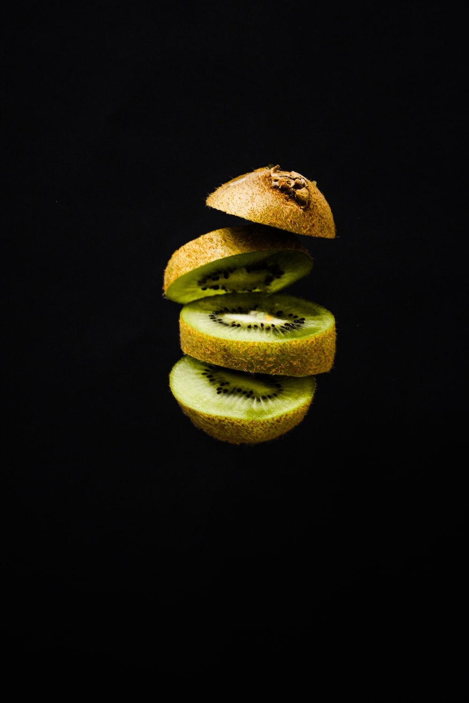 sliced green fruit on black background