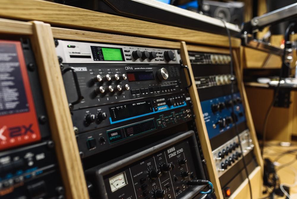 black audio mixer in brown wooden shelf