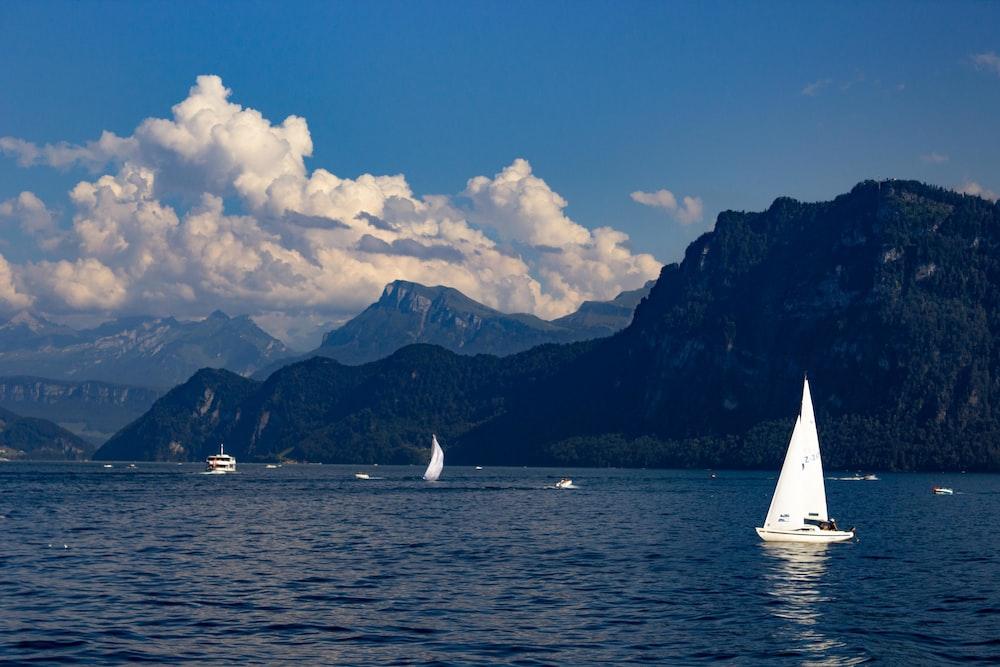 white sailboat on sea near mountain under blue sky during daytime