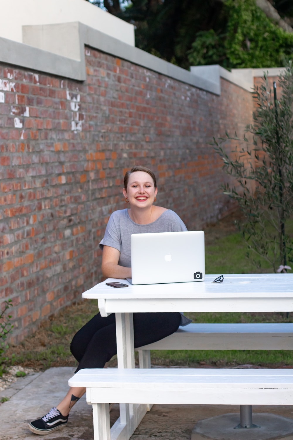 woman in black shirt sitting on white table using silver macbook