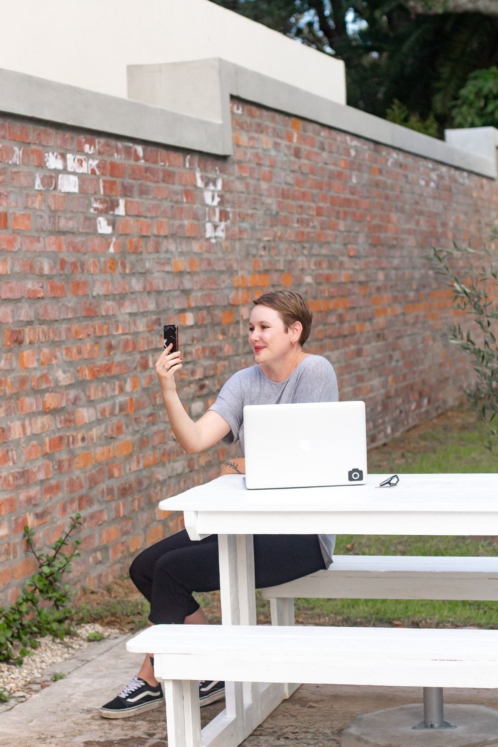 woman in gray shirt sitting on chair using macbook