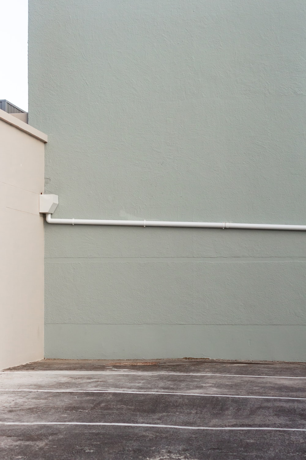 white pipe mounted on green wall