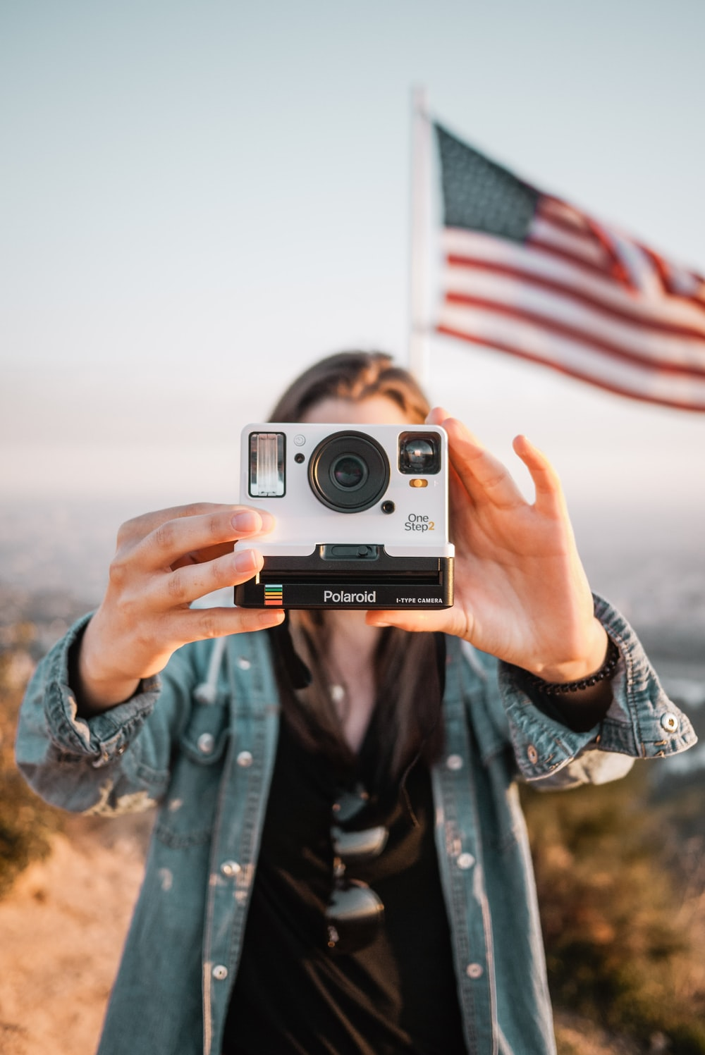woman in blue denim jacket holding silver and black camera