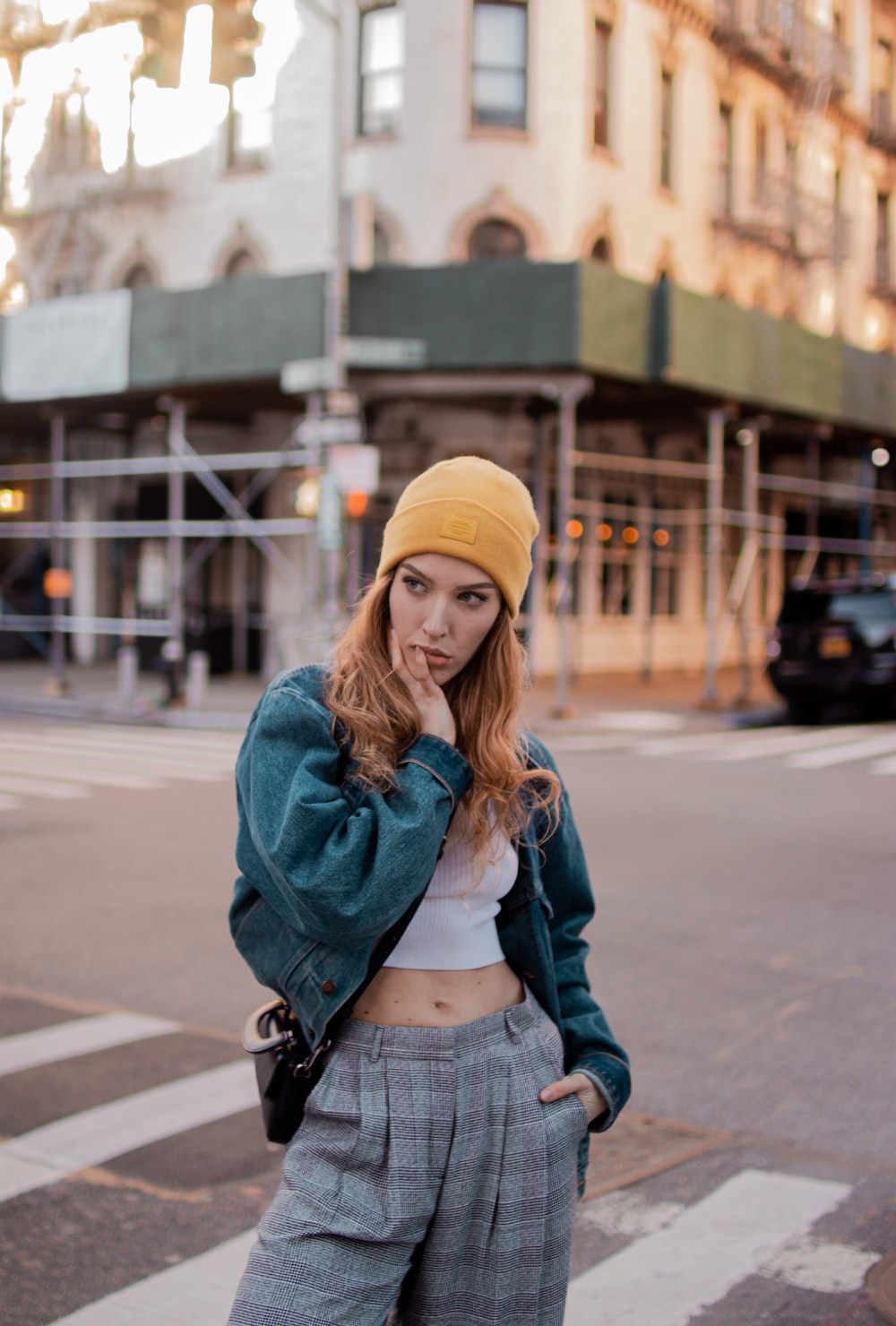 woman in blue denim jacket and yellow knit cap standing on sidewalk during daytime